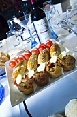 A tray of spicy pastries, boiled eggs, kebabs and a bottle of red wine