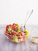 Tomato salad in glass bowl with salad servers