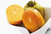 Kaki persimmons, whole and halved