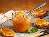 Peach jam in jar and on slices of bread