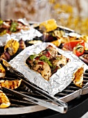 Chicken in aluminium foil on barbecue rack