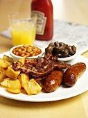 Cooked breakfast: sausages, bacon, fried potatoes, baked beans