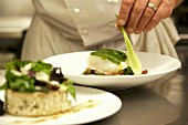 Chef garnishing halibut with spring onion