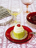 Small marzipan cake with cream and cherry