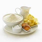 Various baking ingredients (flour, sugar, eggs, butter, milk)