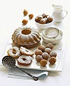 Ring cake, apple fritters and dough balls with icing sugar