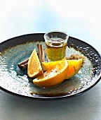 Glass of tequila with cinnamon and oranges on plate