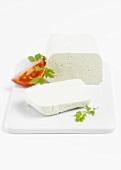 Tofu, angeschnitten, mit Petersilie und Tomatenscheibe auf Porzellanplatte