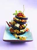 Aubergine tower with tofu, peppers, tomatoes, chilli, oregano