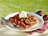 Piece of plum cake with cream on plate