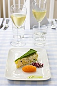Piece of vegetable terrine with accompaniments and white wine
