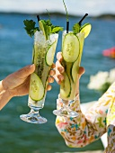 Two women raising glasses of cucumber drink (out of doors)