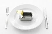 Sardine tin and oil on white plate