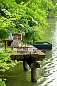 Fishing tackle and picnic hamper on a landing stage