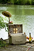Picnic hamper and a bottle of white wine on a landing stage