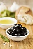 Black olives in dish, olive oil, white bread