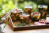 Several jars of pickled summer vegetables on tray