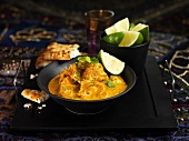 Chicken curry with lime wedges and flatbread (India)