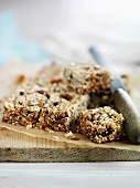 Home-made muesli bars on chopping board with knife