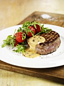 Fillet steak with pepper sauce, cherry tomatoes and rocket