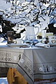 Laid table in wintry garden (Christmas)