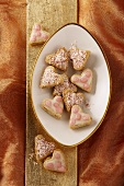 Coconut hearts & heart-shaped iced biscuits on plate (Xmas)