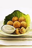 Deep-fried Brussels sprout balls on savoy cabbage leaf with sauce