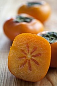 Persimmons, whole and a slice