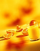 A glass of orange juice, orange halves and wedges
