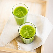 Two wheatgrass drinks on tray