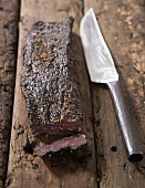 Biltong (dried beef, S. Africa) on wooden background with knife