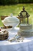 Crockery, cutlery, bread and nuts on table in garden