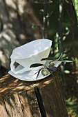White soup cup with olive branch on tree stump
