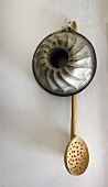 Old ring cake tin and wooden ladle (wall decoration)