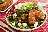 Salad with fresh goat's cheese, pomegranate and bacon rolls