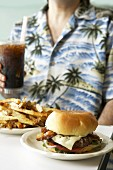 Person with cheeseburger, chips and cola