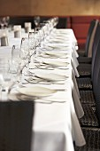 Laid table with white plates, cutlery and wine glasses