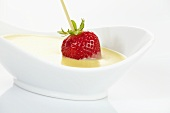 Dipping strawberry on cocktail stick in white chocolate sauce