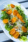 Salad leaves with yellow tomatoes, sprouts, rocket & radishes