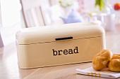 Bread bin and bread rolls on breakfast table