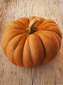An orange pumpkin on a wooden background