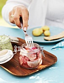 Woman spearing a pickled herring in a jar with a fork