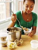 Woman putting cereal into containers to take away