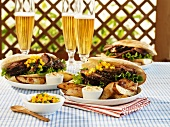 Pork sandwiches with mango salsa & potato wedges, glasses of beer