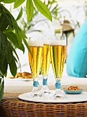 Glasses of beer and nibbles on wicker table