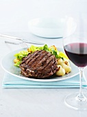 Rib eye steak with onions & romaine lettuce, glass of red wine