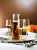 Beer in carafe and glass on laid table