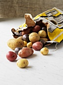 Various types of potatoes falling out of paper sack