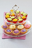Cupcakes and cream tarts on tiered stand