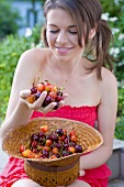 Young woman holding straw hat full of sweet cherries